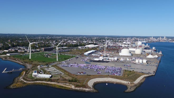 A photo visualization of what the new wind turbines in Providence would look like. The three new turbines are pictured on the left side of the image and in the foreground. Three existing turbines stand in the background to the right.
