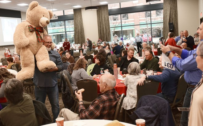 At last year's Brunch Bunch, Darrin Hartman shows off a large bear he won in the annual holiday auction aimed at raising money for several charitable organizations in Portage County. The auction has been canceled this year, but area residents can still donate to a fundraising campaign organized in its place.
