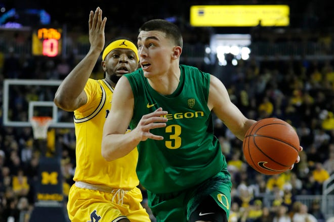 Oregon's Payton Pritchard (3) drives past Michigan guard Zavier Simpson during the second half of the Ducks' Dec. 14, 2019, overtime win over the Wolverines in Ann Arbor, Mich.