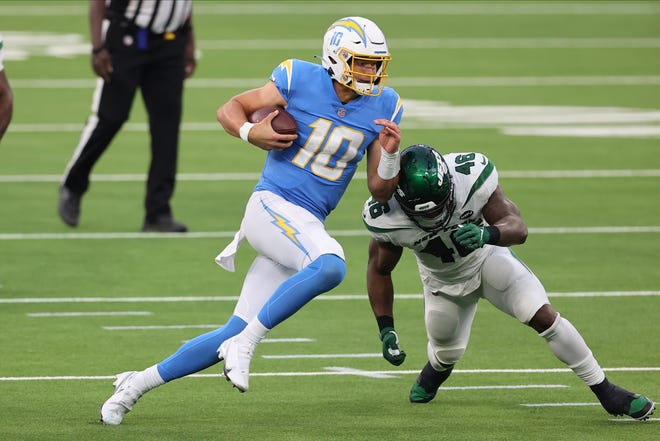 Los Angeles Chargers quarterback Justin Herbert (10) tries to avoid New York Jets linebacker Neville Hewitt during Sunday's win in Inglewood, Calif.