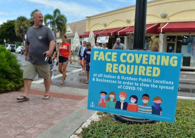 Shoppers walk past stores and restaurants on St. Armands Circle after a brief rain shower on a Wednesday in July. The St. Armands Circle Association is hoping Small Business Saturday will give the area a boost in business.