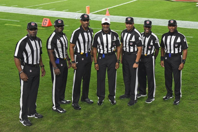 NFL officials, from left, umpire Barry Anderson, field judge Anthony Jeffries, down judge Julian Mapp, referee Jerome Boger, back judge Greg Steed, side judge Dale Shaw (104), line judge Carl Johnson (101) pose for a photo before an NFL football game between the Tampa Bay Buccaneers and the Los Angeles Rams Monday, Nov. 23, 2020, in Tampa, Fla. The game is the first in NFL history to feature an all African-American officiating crew.