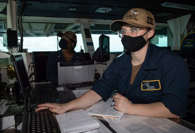 Quartermaster Seaman Marissa Speary, from Winnabow, N.C., tracks the ship's log on the bridge of the aircraft carrier USS Nimitz (CVN 68).