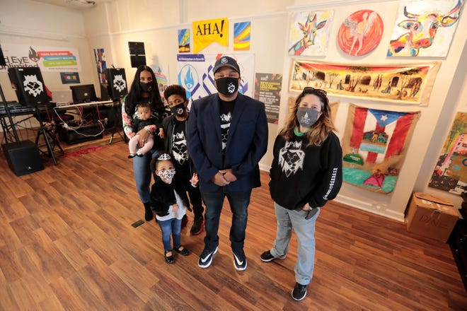 Peter Walker, center, is joined by his family (l to r) Samia Walker, Egypt Walker, 3 months, Amadeus Walker, 11, Nyla Walker, 3, and Keri Cox, 3rd Eye President at The Communal Space on Union Street in New Bedford.