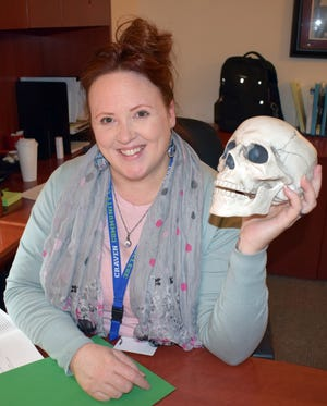 """Craven CC Criminal Justice program instructor LauraAnn Avery, holding class prop """"Fred the Head,"""" recently became the program coordinator and is helping retain its award-winning status. [CONTRIBUTED PHOTO]"""