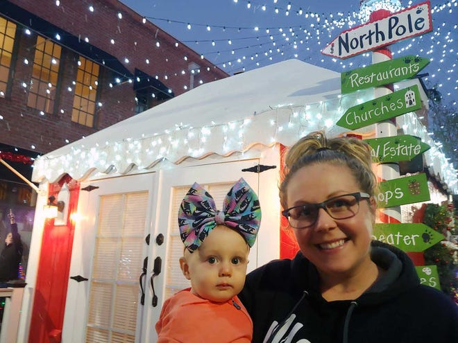 Allison Knight and her 9-month-old daughter McKenzie are ready foir Santa, going by to look at his house in Bear Plaza recently while lights were being tested.