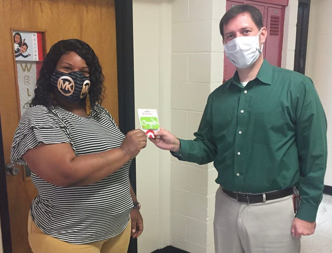 Rhonda Spivey at H.J. MacDonald Middle School accepts a $250 Target gift card from Mike Swain, assistant principal at HJM, as the winner of the drawing for joining PIE during the PIE Membership Drive as a Beginning Teacher! Congratulations, Ms. Spivey, and welcome to Craven County Schools!  For more information on the PIE Membership Drive, visit www.CravenPartners.com. [CONTRIBUTED PHOTO]