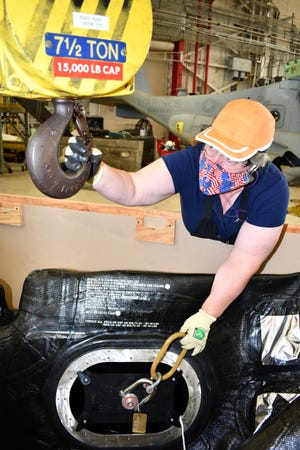 """D.J. Bowman, an aircraft worker on the V-22 line at Fleet Readiness Center East, prepares to connect a crane to the V-22 sponson fuel bladder sling, which is secured to a V-22 Osprey's sponson fuel bladder that arrived at FRCE in a crate. FRCE worked with private industry to develop the new sling, also called a """"dog bone,"""" which helps artisans lift and move the fuel bladders more safely and efficiently. The sling in use at FRCE is the first in the Department of Defense. [Photo by Heather Wilburn, Fleet Readiness Center East Public Affairs]"""