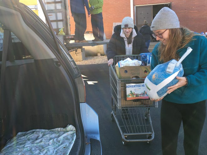 Killingly residents Alundra Hooper and Meg Dion ferry donated food to vehicles during the Friends of Assisi Thanksgiving food distribution event on Tuesday.