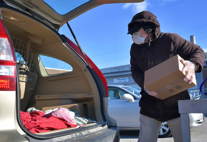 Meals on Wheels volunteer Simon Waters loads his car with meals outside Elder Services of Worcester Area Tuesday