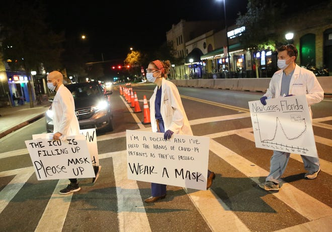 Dr. Ellery Altshuler, center, Dr. Madeline Smoot, second from right, and Jordan Zeldin, right, a medical student, cross Main Street as they worked to raise awareness about the need to wear masks as a protection against COVID-19, downtown on Nov. 20, 2020.