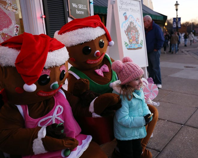 Everly Rankin, then 4, poses with the gingerbread couple during last year's Christmas in the Village. The city of Canal Winchester announced Dec. 1 the drive-thru visits with Santa Claus had been canceled but the Santa parade and BrockStrong Light Up The Night Parade will be held.