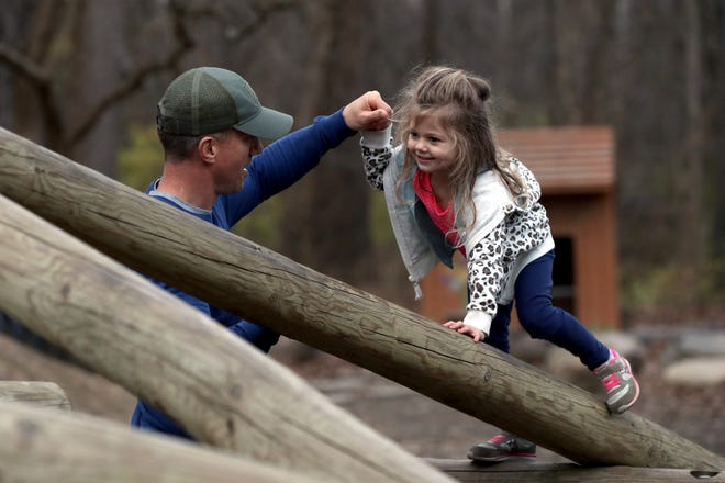 Brad Bell of New Albany helps his daughter, Murphi, 3, navigate a natural playground structure Nov. 20 at Woodside Green Park, 213 Camrose Court in Gahanna.