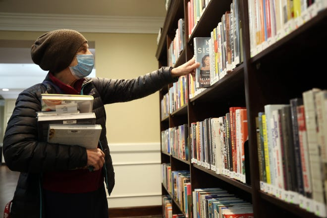 Bexley resident Chani Capland browses through books after picking up others she had on reserve Nov. 18 at the Bexley Public Library. The library had been open for limited services and browsing but was suspended again Nov. 21. The pause will continue until at least Dec. 20.