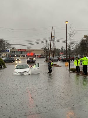 Swampscott firefighters and police could be seen assisting a bundled-up woman whose car got stuck outside Marshall's in a section of flooded-out Vinnin Square around 10 a.m. on Nov. 23.