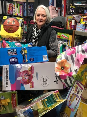 Children's Holiday Fund administrator Sue Giovanetti shows some of the toys collected for needy families this holiday season.