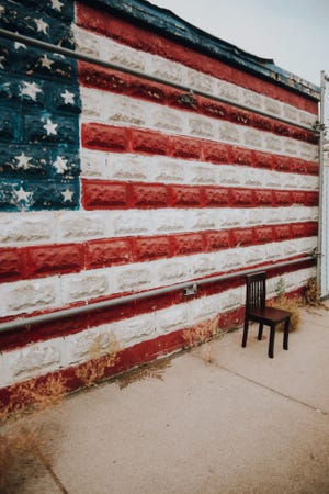 """""""I see it in the flag painted on the wall where the chair sits, the flag that is supposed to represent freedom and safety, hasn't felt like that lately,"""" said artist Kathlyn Almeida in her statement."""