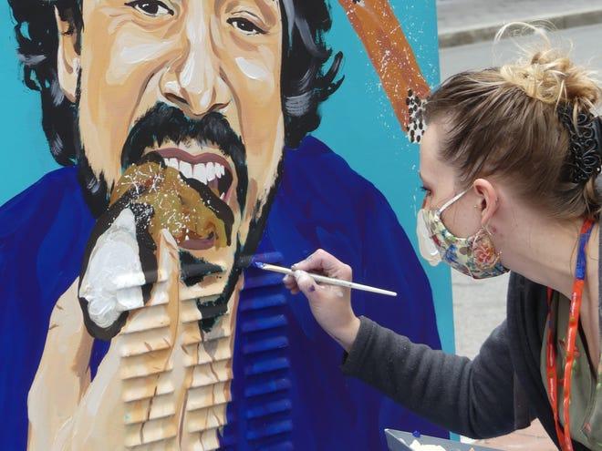 Medford artist April Jakubec works on a Boston street painting a utility box for Tasteful Boston's art project.