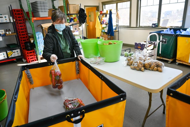 Claudette Chmura removes a bag of apples from a bin while helping to package perishables for meals at the The Open Door food pantry in Gloucester as they prepare for the holiday season and the needs of the community amid the coronavirus pandemic on Tuesday, Nov. 24.