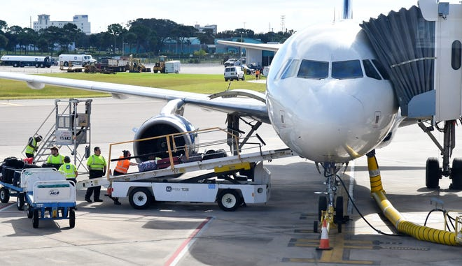 A Delta Air Lines flight is loaded with luggage this week at Orlando Melbourne International Airport.
