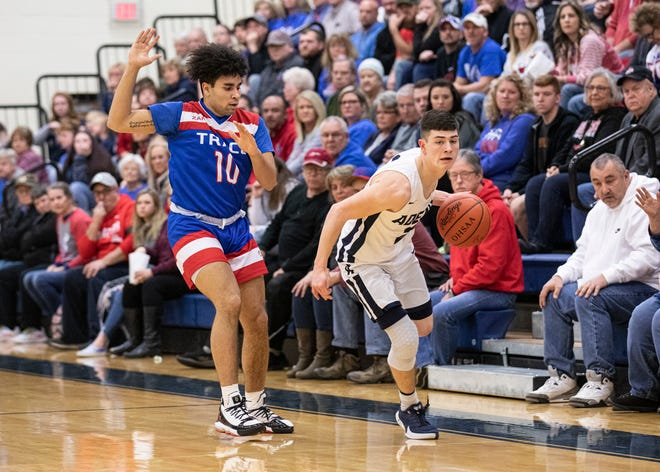 Adena's Nate Throckmorton attempts to drive the ball past Cam Evans as a gym full of spectators watch during a home game at Adena last year. Adena, along with other Ross County schools, will be limiting the number of spectators this year due to the coronavirus pandemic.
