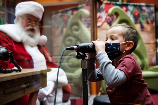 """Carter Coughlin, 3, tells Santa what he wants for Christmas at Valley West Mall on Nov. 24, 2020, in West Des Moines Iowa. The mall built an addition to its train station and calls it """"Santa's Office,"""" with a Plexiglas wall and speaker system, to increase safety for kids who visit Santa."""