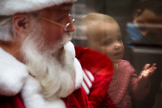 """Kate Coughlin, 1, blows a kiss to Santa in his """"office"""" at Valley West Mall on Nov. 24, 2020, in West Des Moines, Iowa. The mall built an addition to its train station, with a Plexiglas wall and speaker system so kids could visit with Santa safely."""