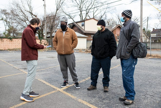 Here to Help CEO Bob Schwartz, left, speaks with returning citizens Eric Thompson, Curtis Manier and Jamel Robinson, all of Detroit, during a meeting to help them with their everyday needs after prison at a parking lot in Royal Oak on Thursday, Nov. 19, 2020.