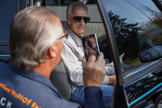 Dennis Wallace of Taylor takes a photo of retired Ford Escort designer Jack Telnack as he sits in Wallace's 1986 Ford Escort GT.