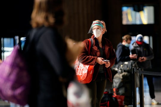 A woman waits in line for a train at the 30th Street Station ahead of the Thanksgiving holiday, Friday, Nov. 20, 2020, in Philadelphia.