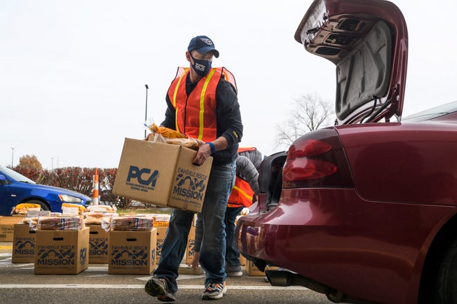 Tyler Fruit loads a box of food into a car during the Evansville Rescue Mission's 99th annual Gobbler Gathering held outside of Old National Events Plaza in Evansville, Ind., Tuesday, Nov. 24, 2020. Due to COVID-19 restrictions. the food giveaway was turned into a drive-up event with distribution times scheduled from 10:30 a.m. to 5:30 p.m.