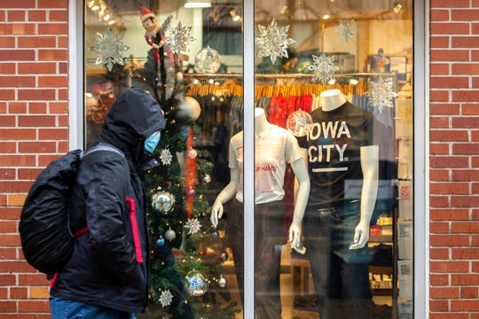 A person wearing a face mask walks past a window at Raygun on Washington Street, Tuesday, Nov. 24, 2020, in downtown Iowa City, Iowa.