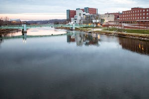 The Iowa Memorial Union, Iowa Advanced Technology Laboratories and Elizabeth Catlett Residence Hall are reflected in the Iowa River, Monday, Nov. 23, 2020, on the University of Iowa campus in Iowa City, Iowa.