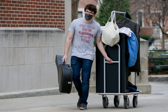 Evan Stavnheim, a senior electrical engineering student, wheels a cart with his belongings towards his car as he moves out of his Purdue University dorm, Monday, Nov. 23, 2020 in West Lafayette.