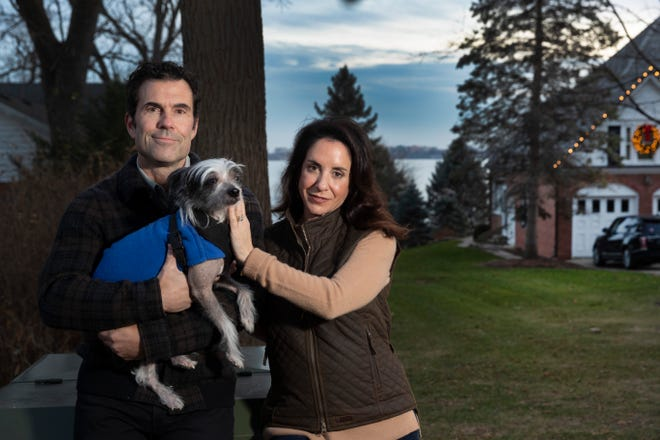 Chris and Trish Cain, along with their dog, Whitman, stand in front of a disputed parcel of land allowing access to Lake Mendota Monday, Nov. 23, 2020, near their home in Maple Bluff, Wis.