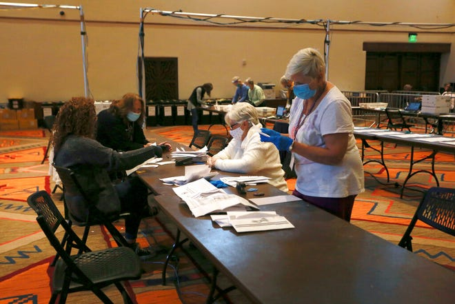 In this Nov. 3, 2020, file photo, election workers sort electronically submitted ballots at the Santa Fe Convention Center on Election Day in Santa Fe, N.M. The state canvassing board has certified Joe Biden's win in New Mexico, delivering the state's five electoral votes to the Democrat. Approval came Tuesday, Nov. 24, 2020, as the board met remotely amid the surging pandemic.