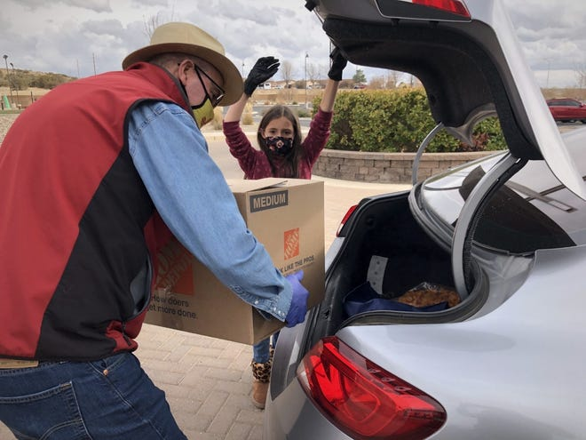 Eden Sanchez and her grandfather Fred Proctor help give out Thanksgiving Boxes of Love at Pinon Hills Community Church in Farmington on Nov. 23, 2020.