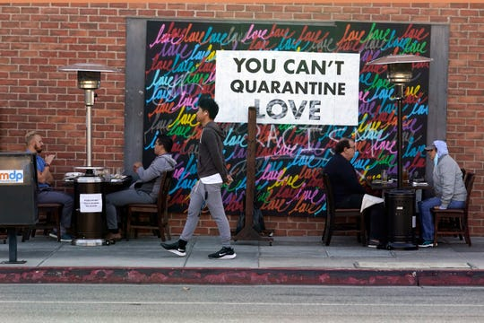 """A COVID-19-themed mural reads """"You Can't Quarantine Love,"""" outside of a restaurant, Monday, Nov. 23, 2020, in Santa Monica, Calif."""