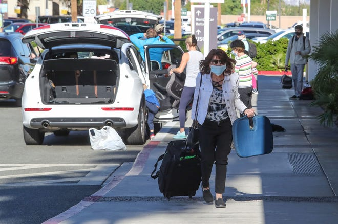 Travelers come and go through Palm Springs International Airport, November 24, 2020.