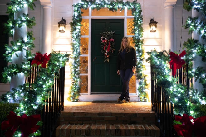 Diane Kaji stands outside the front door of her family's Cedar Lane Drive home. Kaji decided to decorate her home for Christmas early this year to spread a little extra cheer to her family and their neighbors.