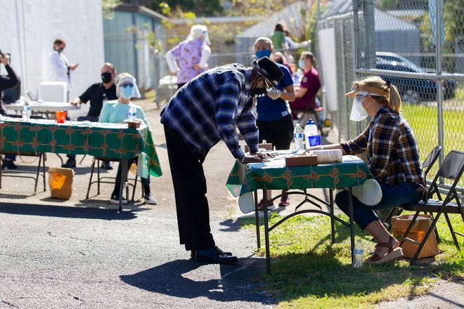 A community member goes through a quick health screening process before receiving an early Thanksgiving meal from Grace Mission Episcopal Church on Tuesday, Nov. 24, 2020.