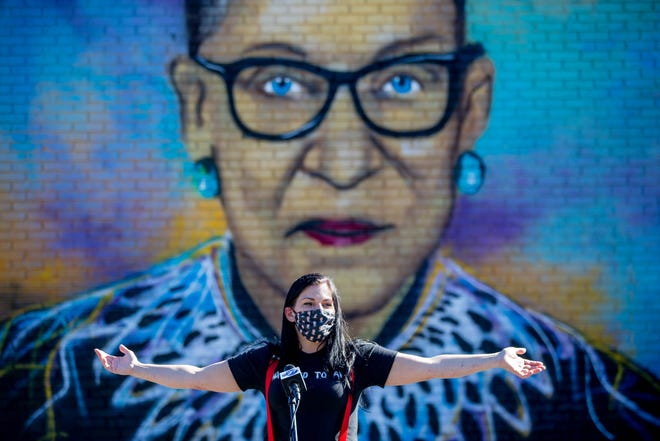 Artist Kollet Hardeman does a TV interview in front of the newest mural of Justice Ruth Bader Ginsburg she painted on the exterior wall of the Florida People's Advocacy Center along with a mural of Rosa Parks after an event was held to reveal the two Tuesday, Nov. 24, 2020.