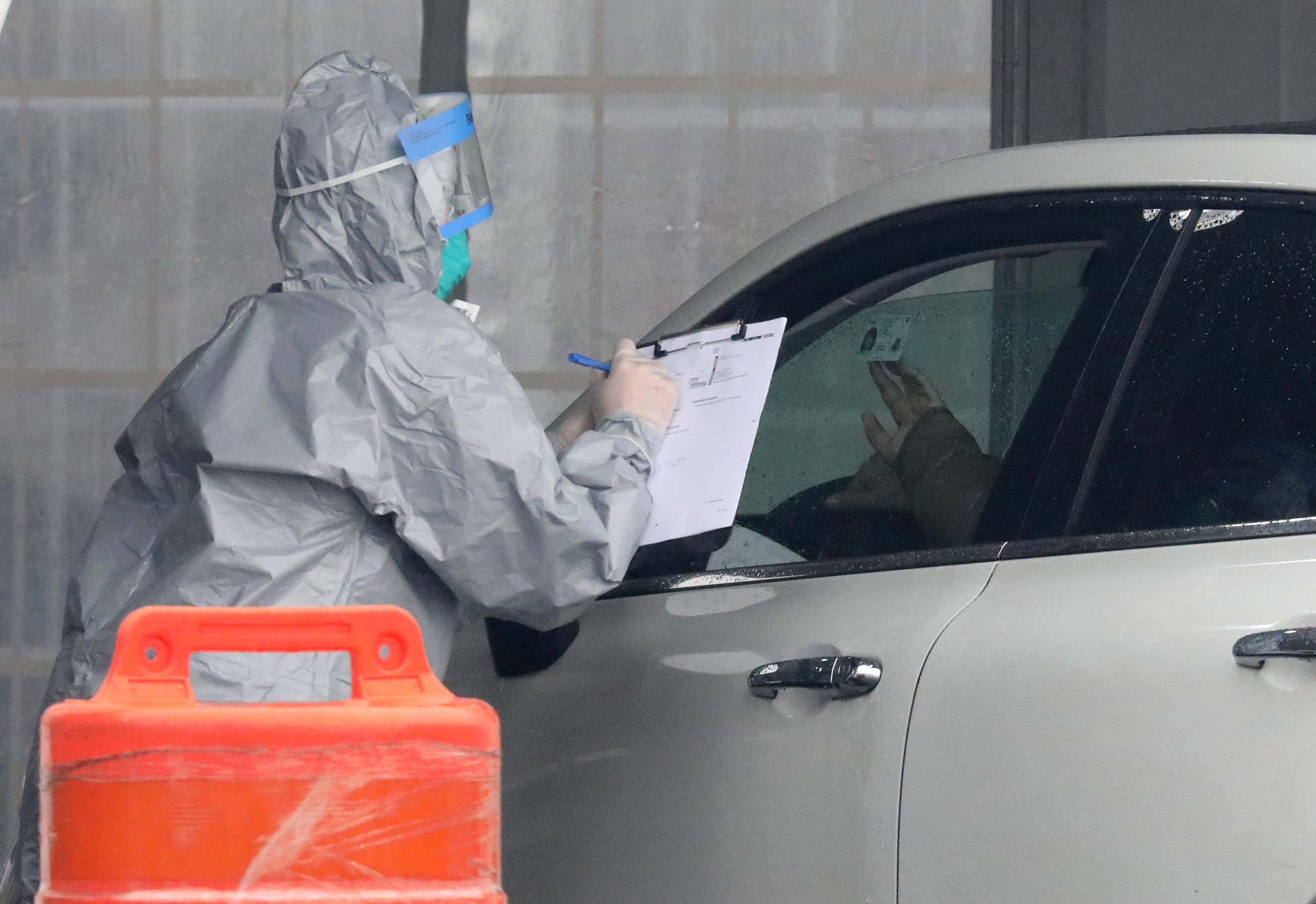A person holds up their ID as a worker in protective clothing gathers information from people that want to get tested, at Glen Island Park in New Rochelle, as New York State's first drive through COVID-19 mobile testing center opens, March 13, 2020.