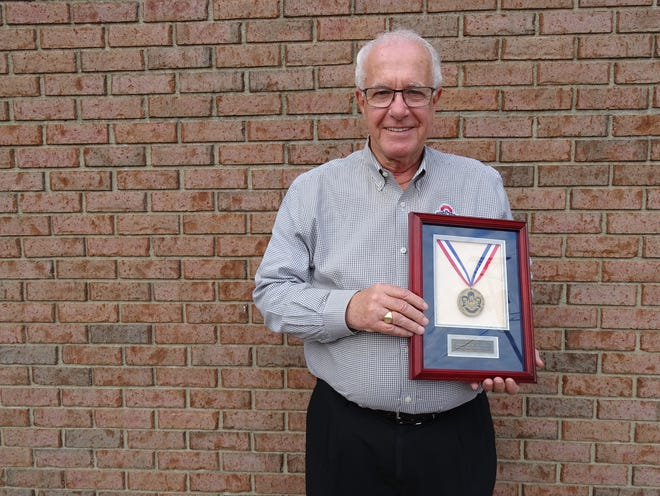 Dean Cole stands with his Muskingum County Military Hall of Fame award outside of his business, Tom's Print Shop in downtown Zanesville.