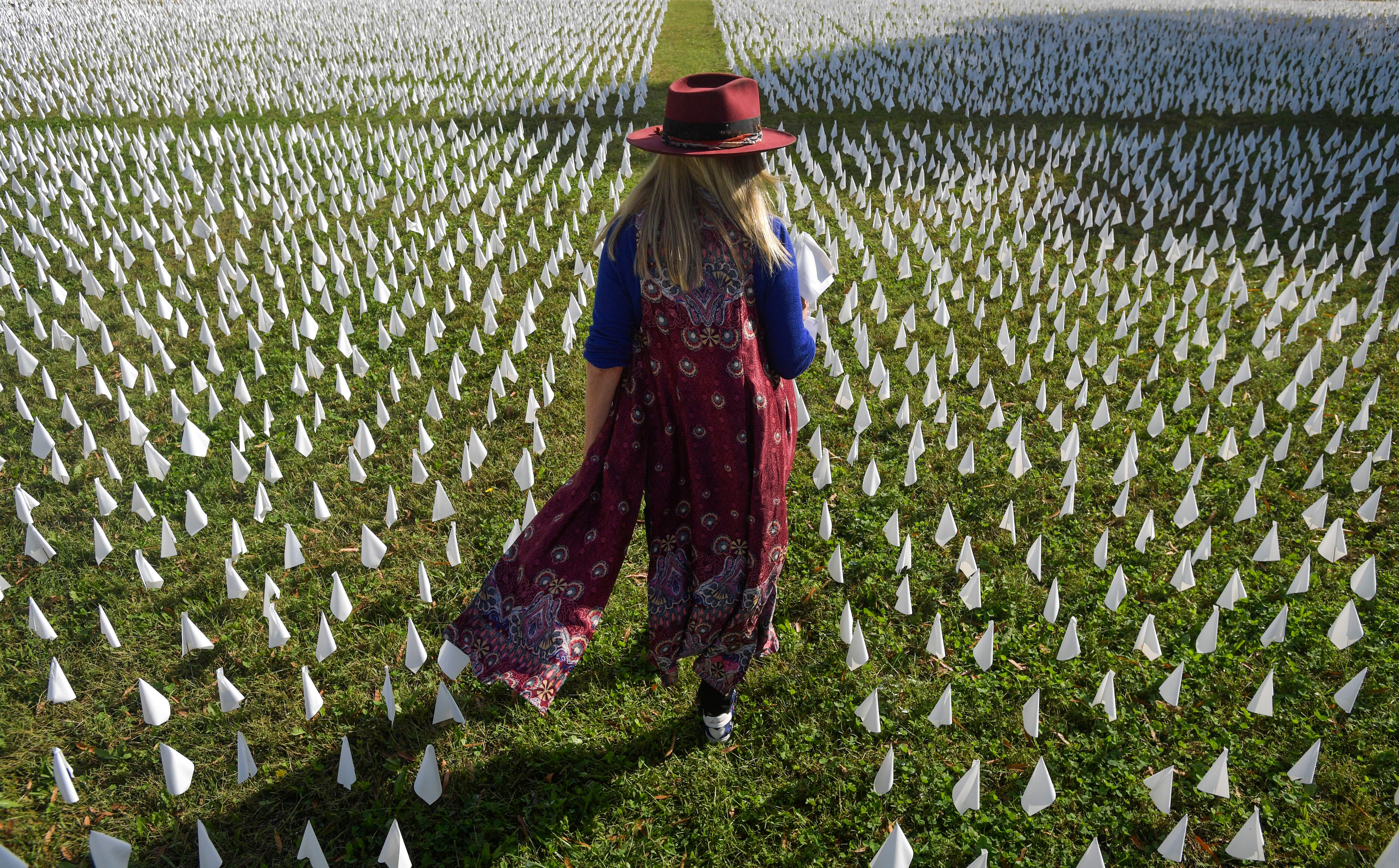 """Artist Suzanne Firstenberg walks through """"IN AMERICA: How Could This Happen,"""" an installation on the DC Armory Parade Ground in Washington, D.C., on Oct. 23, 2020. Each flag represents a life lost to COVID-19 in the United States. At the time of the installation, the number of flags totaled just under 225,000."""