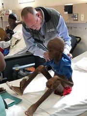 Dr. Paul Farmer treats a boy in Haiti in 2019.