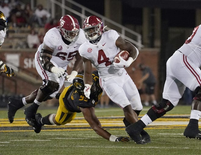 Alabama running back Brian Robinson Jr. (4) runs the ball while avoiding the tackle of Missouri linebacker Z'Core Brooks during a game at Faurot Field at Memorial Stadium.