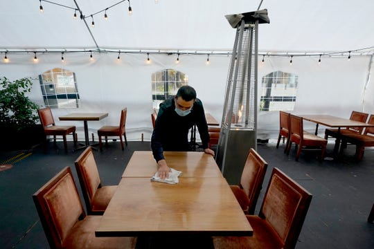Fabian Rodriguez cleans a table in an outdoor tented dining area of Tequila Museo Mayahuel restaurant, in Sacramento, Calif., Thursday, Nov. 19, 2020.