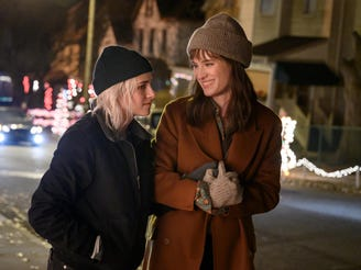 "Kristen Stewart (left) and Mackenzie Davis star as a lesbian couple whose relationship is tested by a holiday family get-together in the romantic comedy ""Happiest Season."""