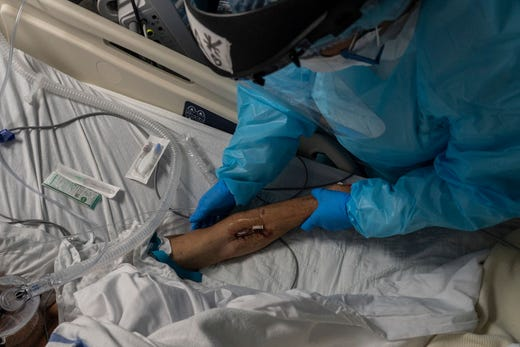 Medical staff member Tanna Ingraham checks I.V. on a patient in the COVID-19 intensive care unit (ICU) at the United Memorial Medical Center on November 19, 2020 in Houston, Texas.